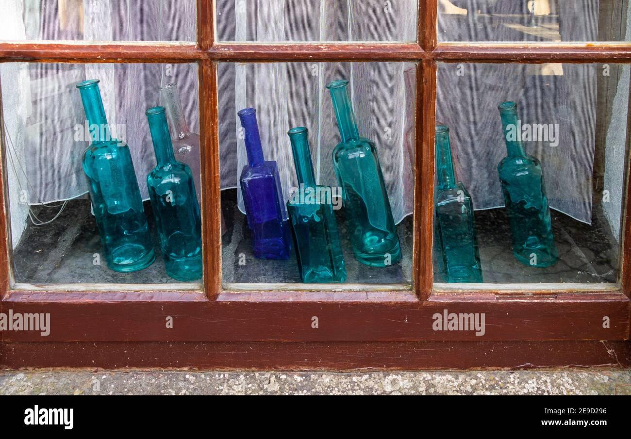 seven-blue-glass-bottles-on-display-on-a-window-sill-2E9D296.jpg