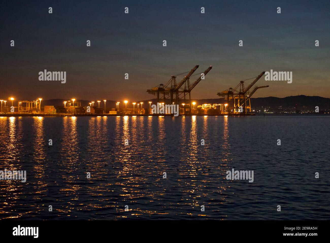 Port of Oakland at sunset. Intermodal shipping containers and cranes in the San Francisco Bay. International trade and commerce. Stock Photo
