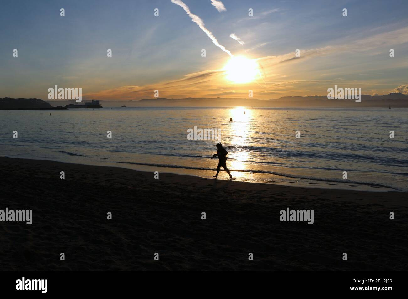 woman-running-in-the-surf-holding-her-shoes-in-her-hands-on-a-sunny-morning-on-the-edge-of-santander-bay-cantabria-spain-winter-2021-2EH2J99.jpg