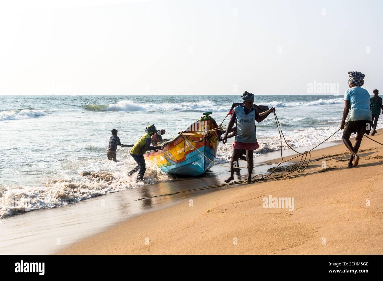 fisherman-pushing-boat-to-land-from-sea-after-returning-from-the-day-work-2EHM5GE.jpg