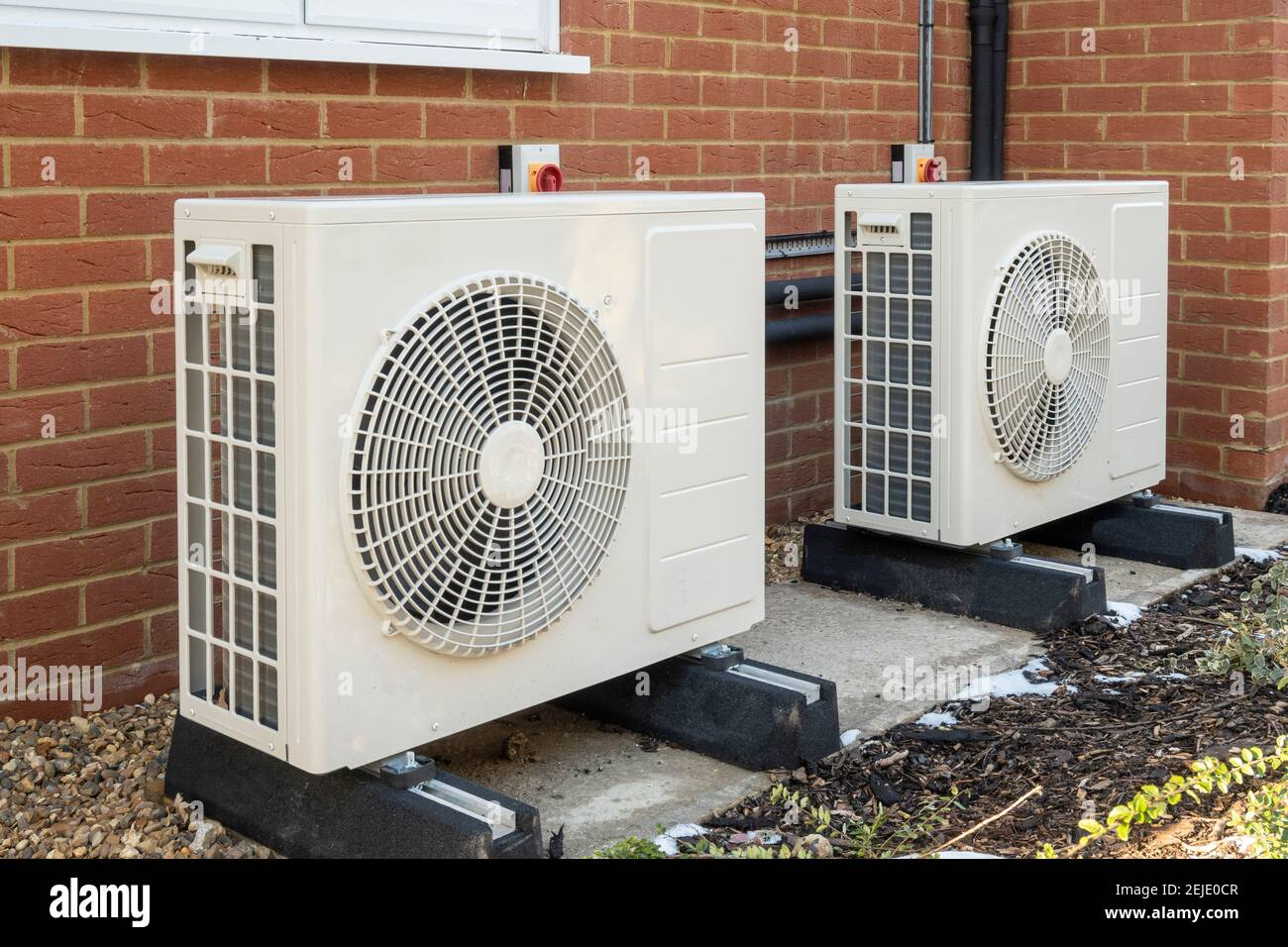 Two air source heat pumps installed on the exterior of a modern house Stock Photo