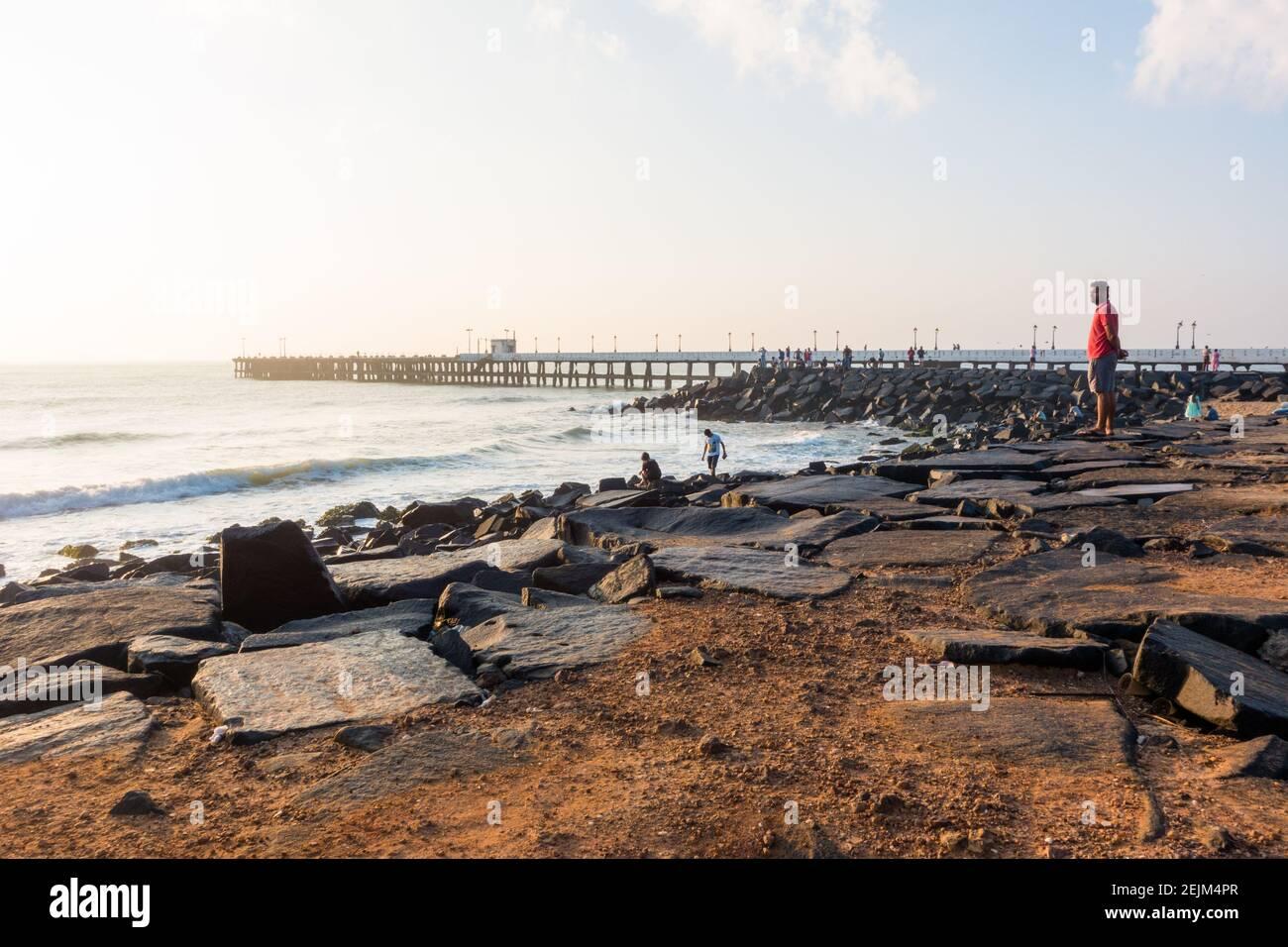 adult-male-watching-sunrise-at-sunrise-point-in-pondycherry-beach-shore-2EJM4PR.jpg