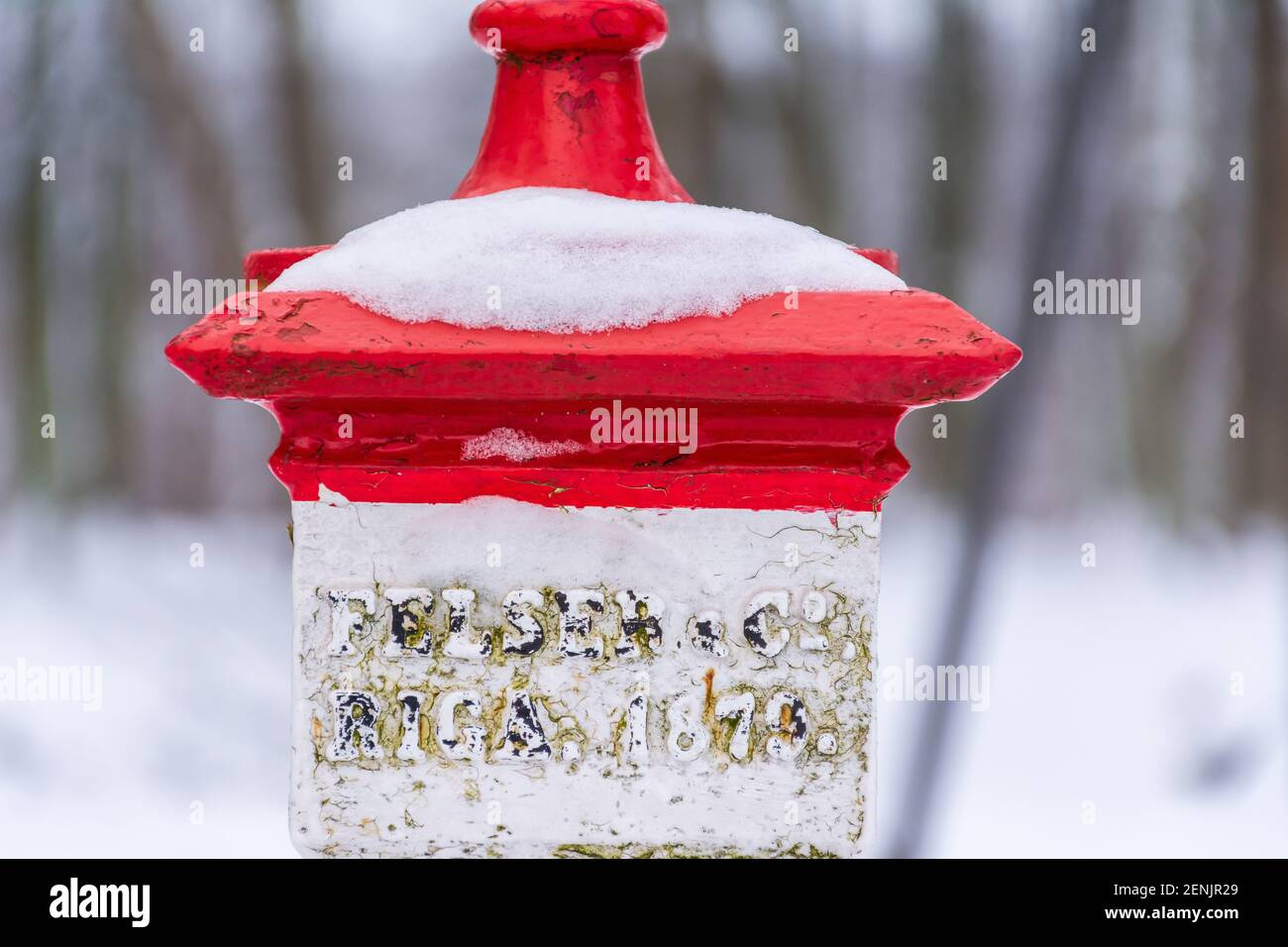 Red and white post with year on of an olld suspension bridge over a gorge  to castle hill in winter in Viljandi Estonia Stock Photo