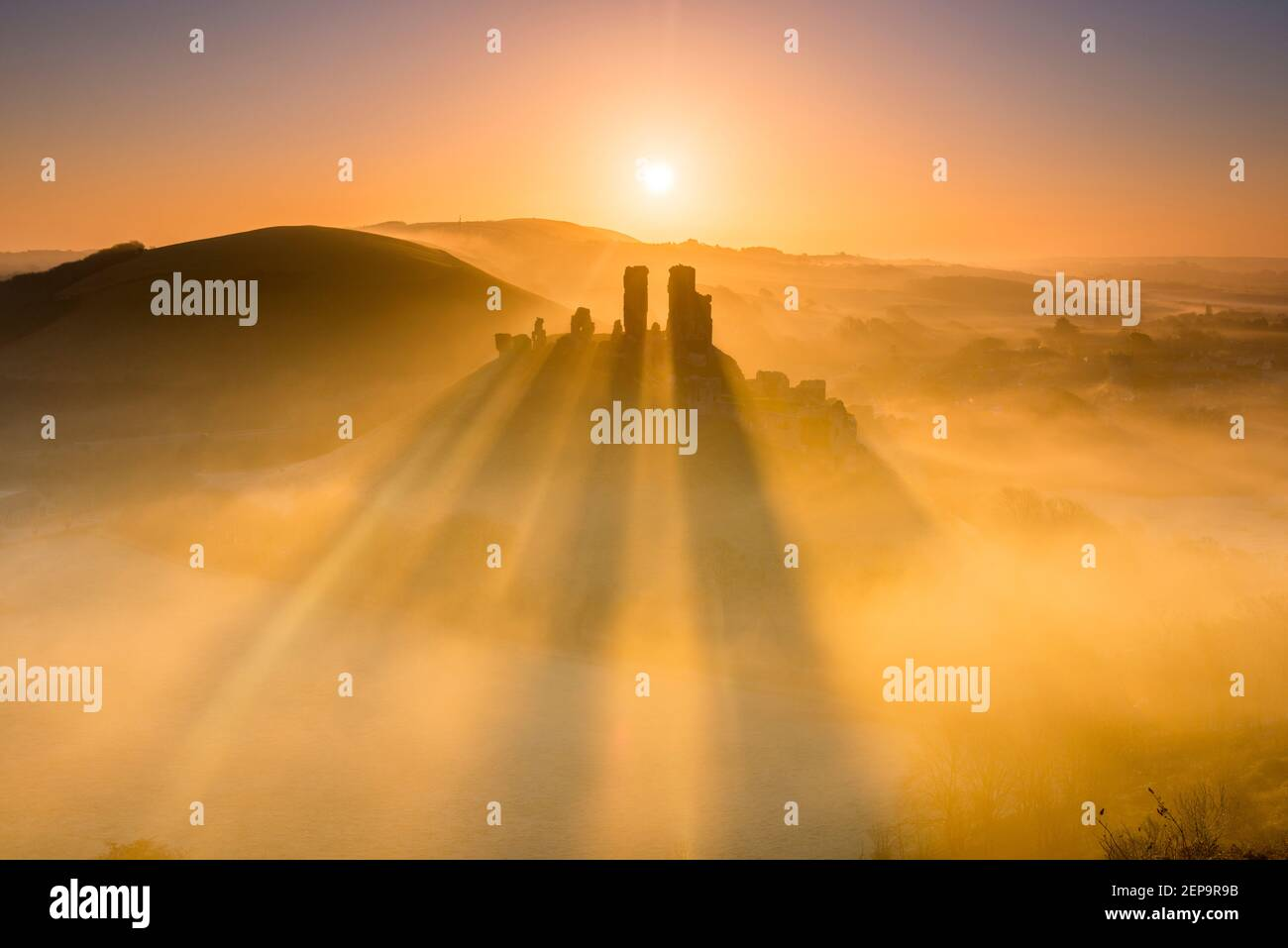 Corfe Castle, Dorset, UK.  27th February 2021.  UK Weather.  A spectacular sunrise with the shadows of the ruined towers on the mist surrounding Corfe Castle in Dorset on a cold frosty morning at dawn.  Picture Credit: Graham Hunt/Alamy Live News Stock Photo