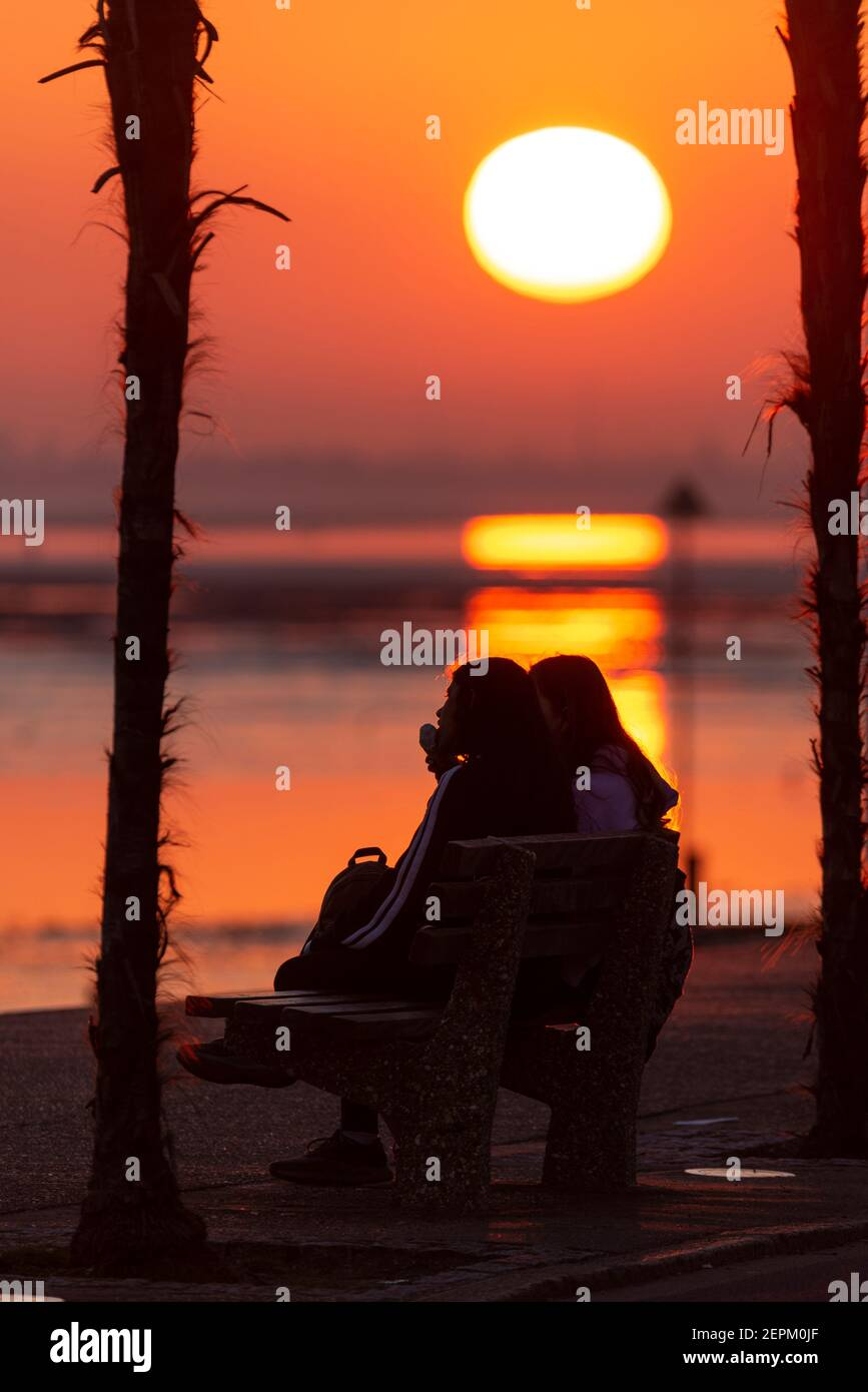 females-eating-ice-cream-at-sunset-silhouette-of-girls-sitting-on-seafront-promenade-together-as-the-sun-goes-down-towards-the-horizon-2EPM0JF.jpg