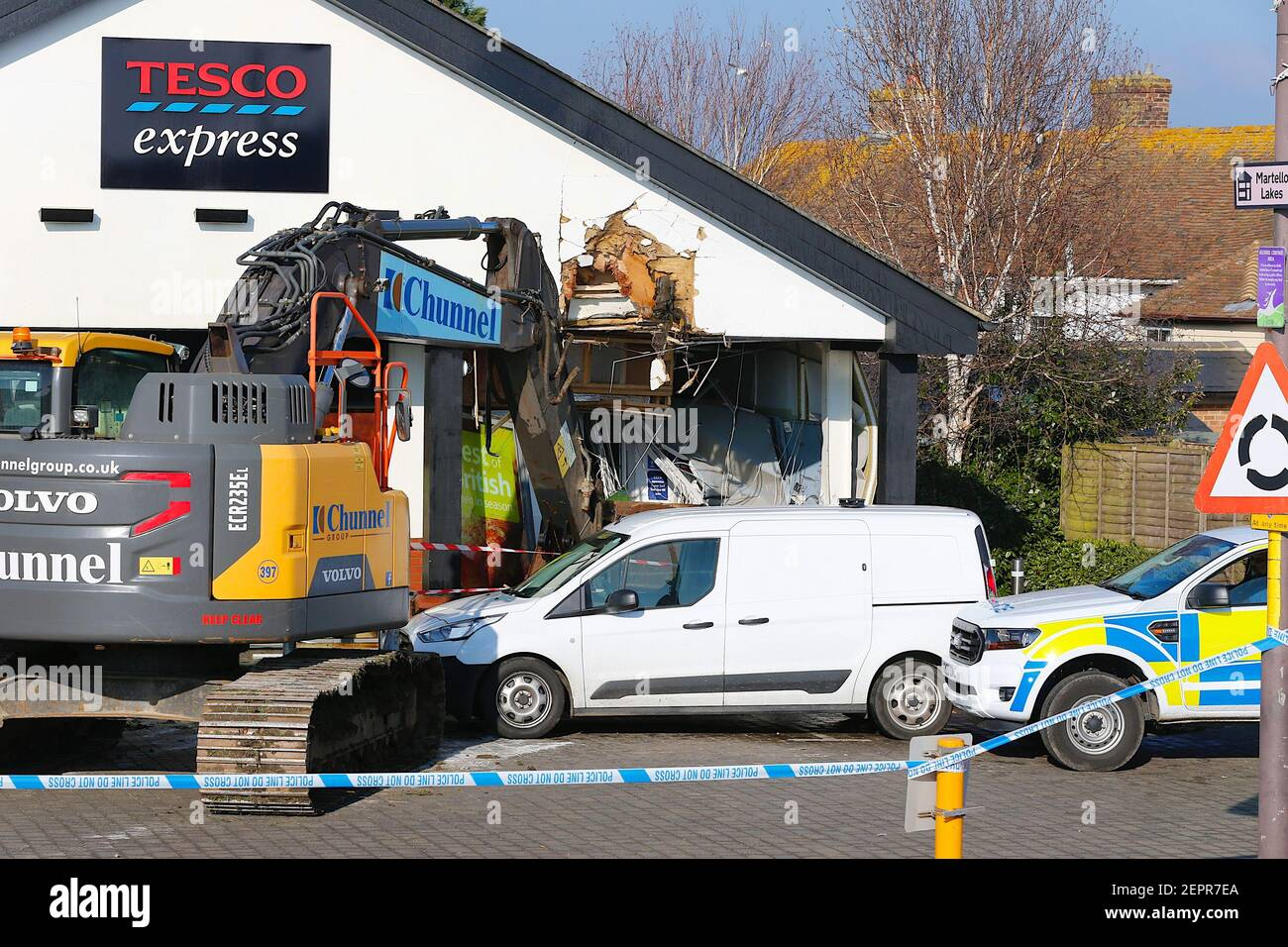 Dymchurch, Kent, UK. 28 February, 2021. Emboldened thief's have attempted a daring raid on this Tesco express in Dymchurch Hugh street having driven a Volvo ECR235E crawler excavator in the early hours of the morning in an attempt to rob the store. According to member of staff, assailants failed to take a cash point as it now lies on the floor with 'loads of money' lying around. A corner of the building lies in tatters. Photo Credit: Paul Lawrenson/Alamy Live News Stock Photo