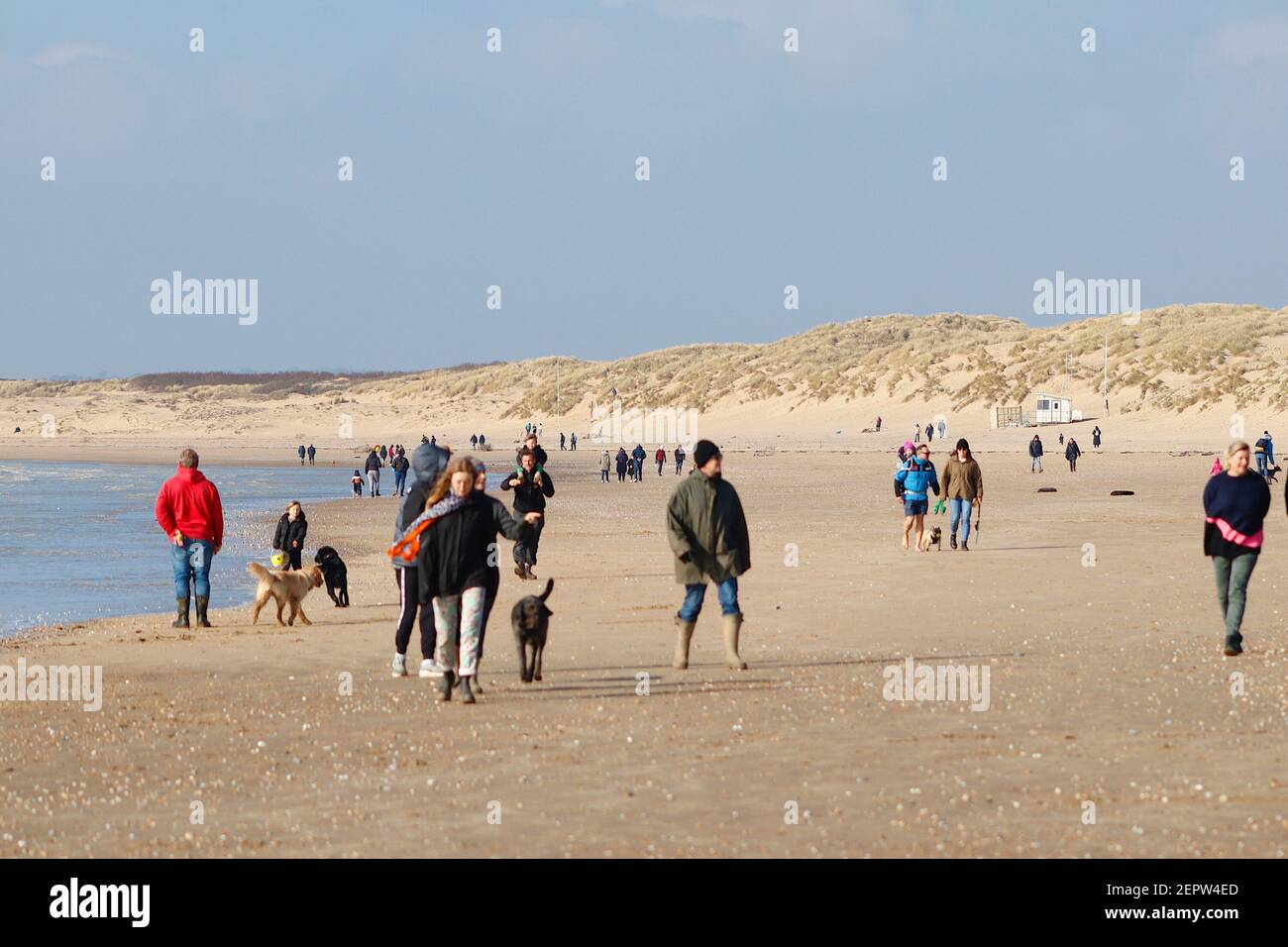 Camber, East Sussex, UK. 28 Feb, 2021. UK Weather: Warm winter sunshine with breezy winds here at Camber Sands in East Sussex. Lots of families and people enjoying the mild winter weather walking along the sandy beach. Large group of people enjoying the fresh air on the golden sands. Photo Credit: Paul Lawrenson/Alamy Live News Stock Photo