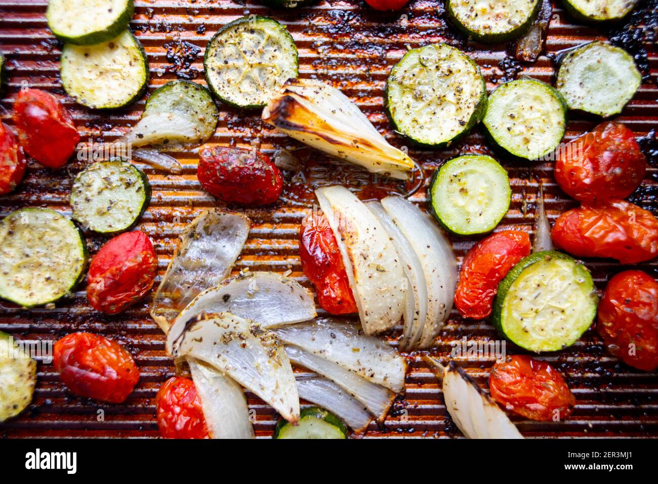 Food Sheet pan roasted vegetables zucchini onions cherry tomatoes Stock Photo