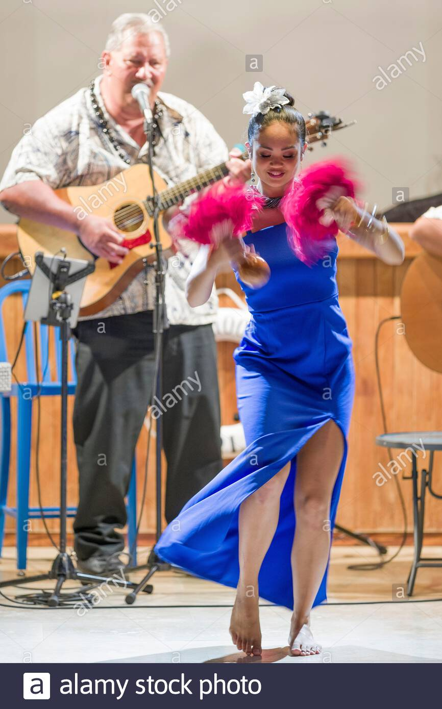 Young woman wearing a blue dress dancing a Hawaiian hula to live music using Uliuli red feather gourds, Honolulu, Oahu, Hawaii, USA Stock Photo