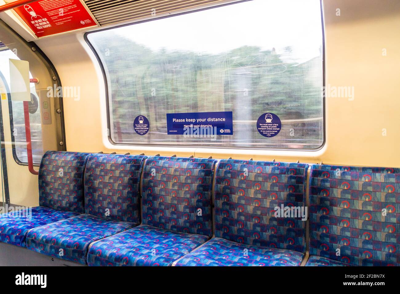 view-through-the-window-of-an-empty-central-line-london-underground-train-with-a-coronavirus-face-covering-warning-sign-2F2BN7X.jpg