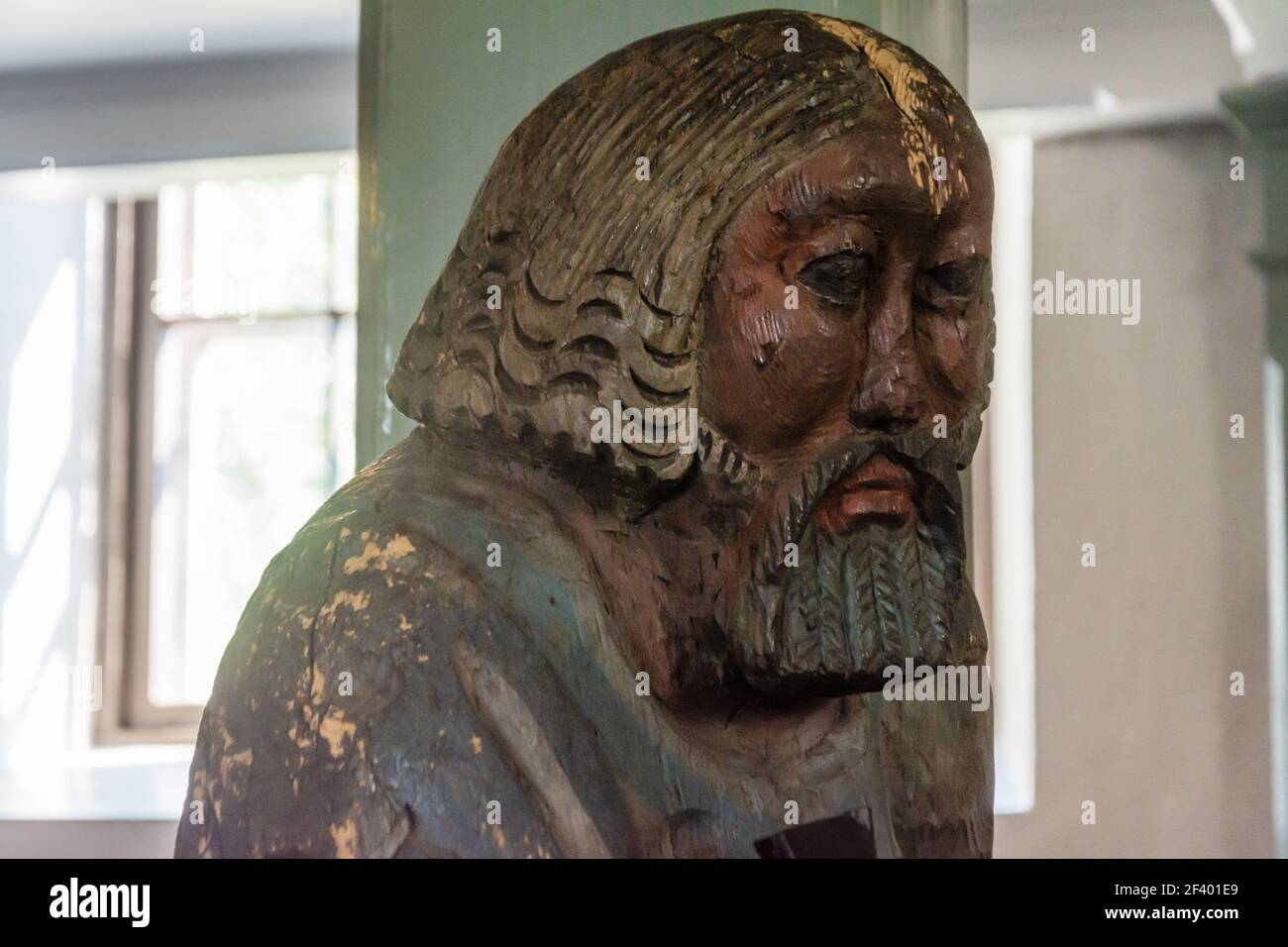 Old wooden pauper statue called Bartimeus of medieval stone church of Hauho Finland Stock Photo