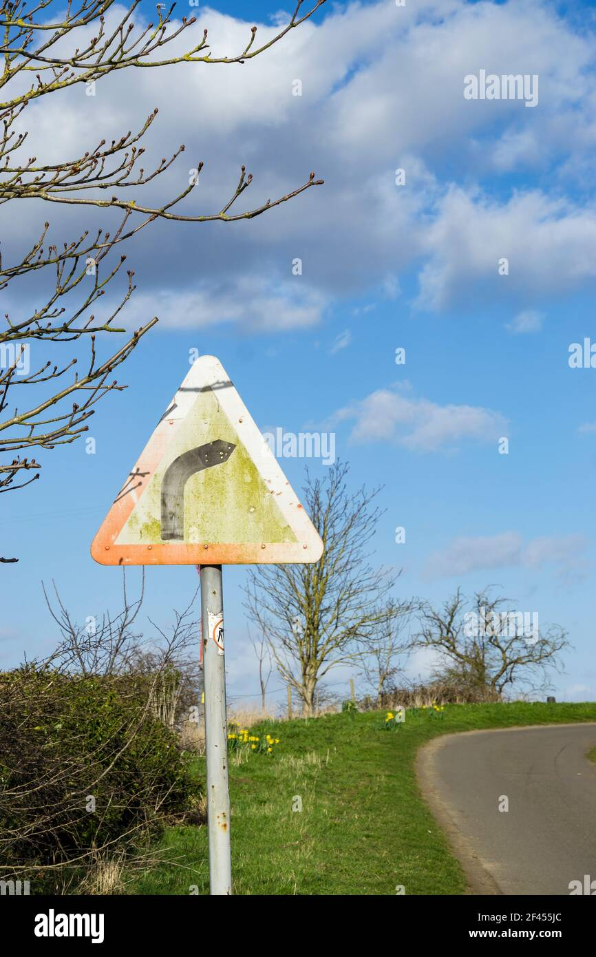 Weathered road sign advising right hand bend Stock Photo