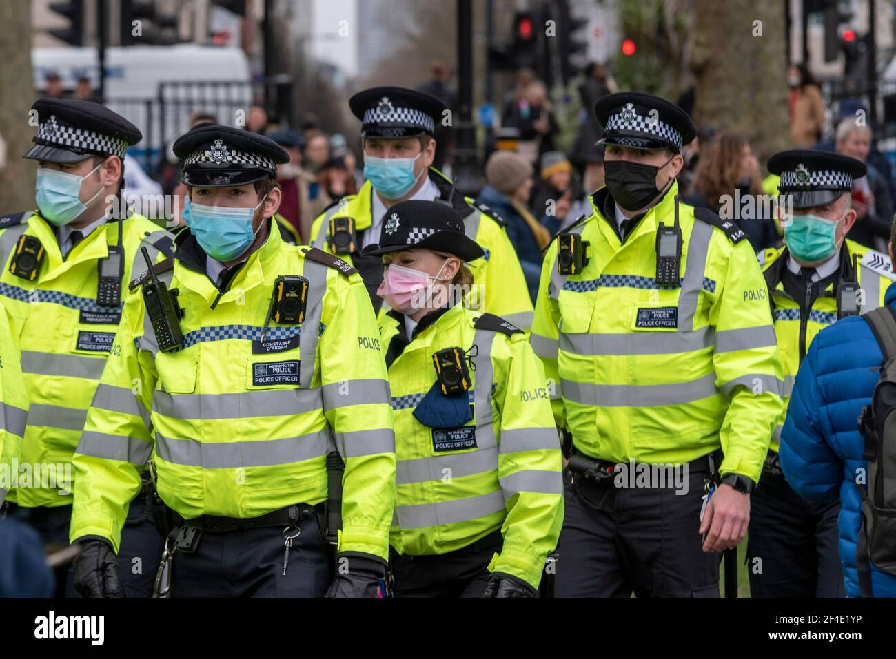 police-arriving-at-an-anti-lockdown-anti-policing-bill-protest-rally-in-london-uk-female-officer-with-pink-face-mask-male-officers-with-blue-mask-2F4E1YP.jpg