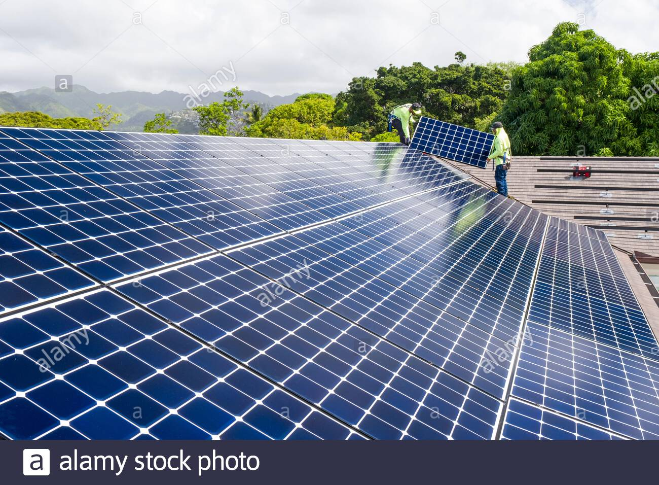 Men wearing safety harnesses standing on roof installing LG NeonR DC photovoltaic panels onto aluminum rails during a residential photovoltaic install Stock Photo