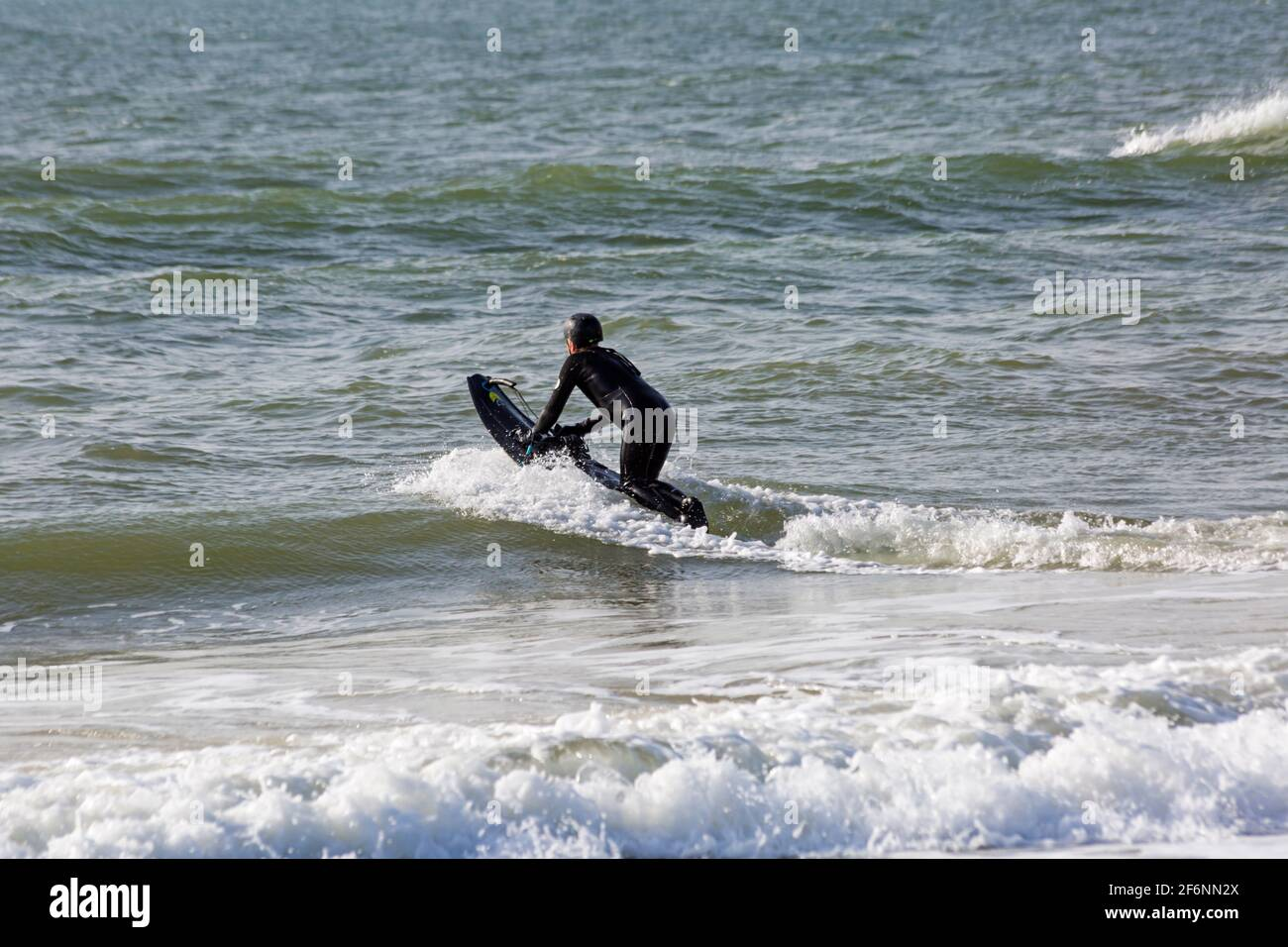 Poole, Dorset UK. 2nd April 2021. Easter Friday. UK weather: sunny, cool and breezy for the start of the long Easter bank holiday weekend at Poole beaches as people head to the seaside. Mako jet boarder makes the most of the conditions before it gets busy. Credit: Carolyn Jenkins/Alamy Live News Stock Photo