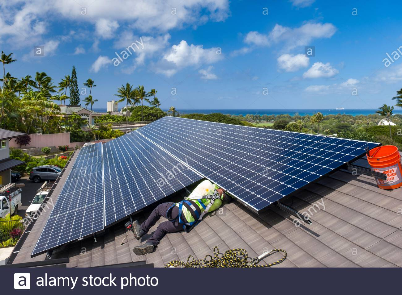 Man laying on rooftop reaching under photovoltaic panel to connected the wiring during a residential installation, Honolulu, Oahu, Hawaii, USA Stock Photo