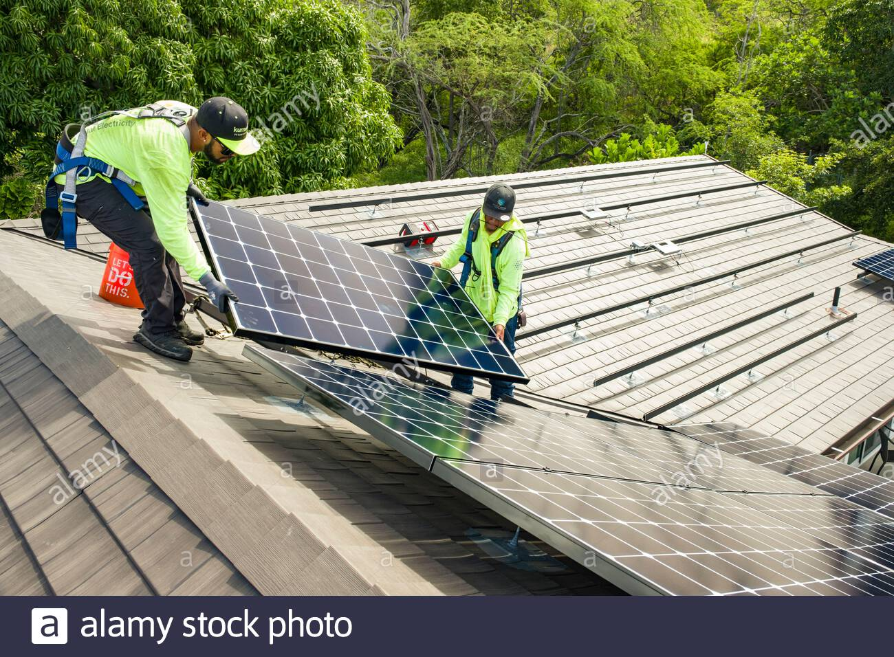 Two men working together to install photovoltaic panel onto aluminum rails on residential rooftop, Honolulu, Oahu, Hawaii, USA Stock Photo