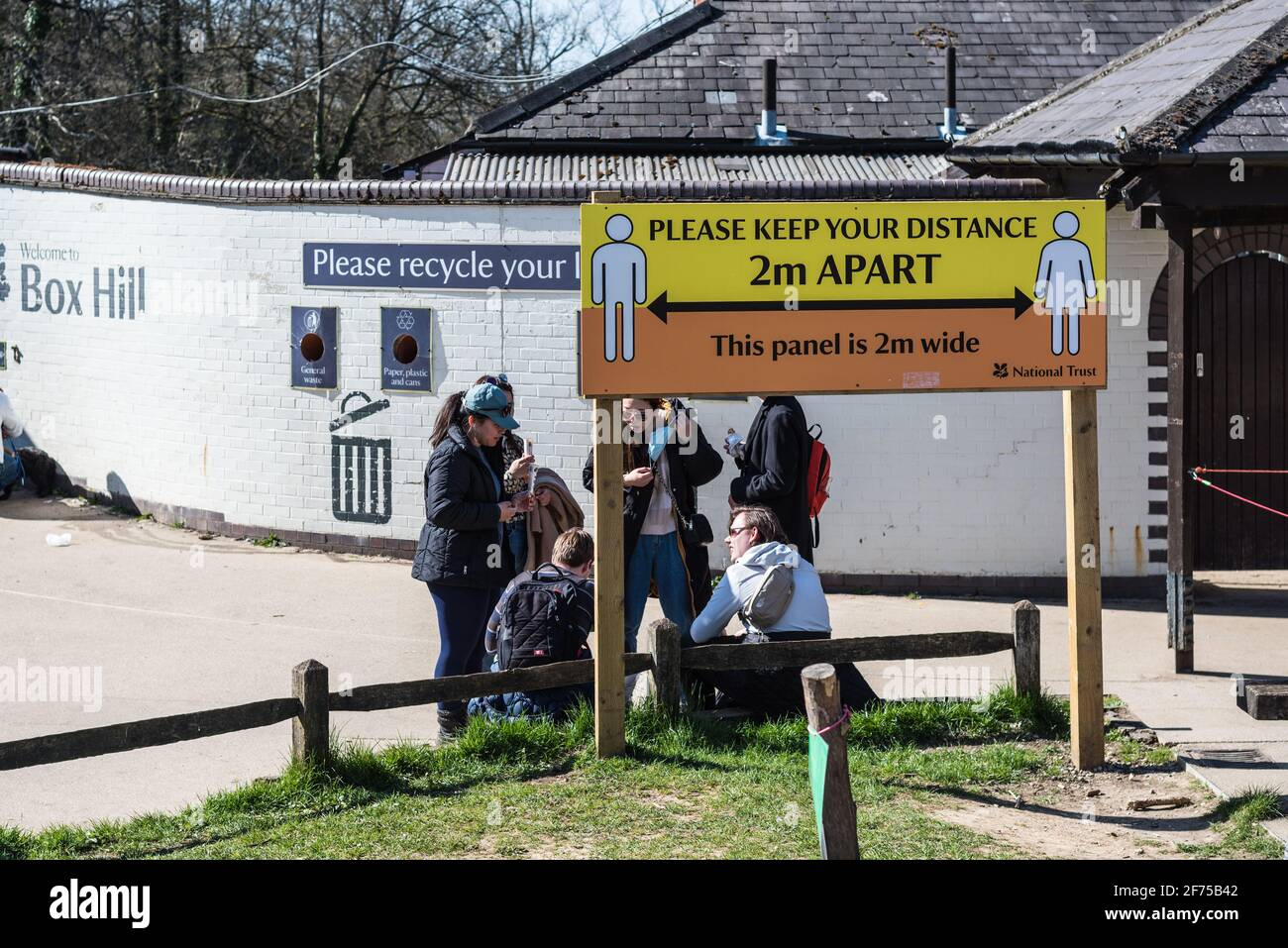 keep-2m-apart-notice-in-national-trust-boxhill-with-people-sitting-under-the-banner-in-group-2F75B42.jpg
