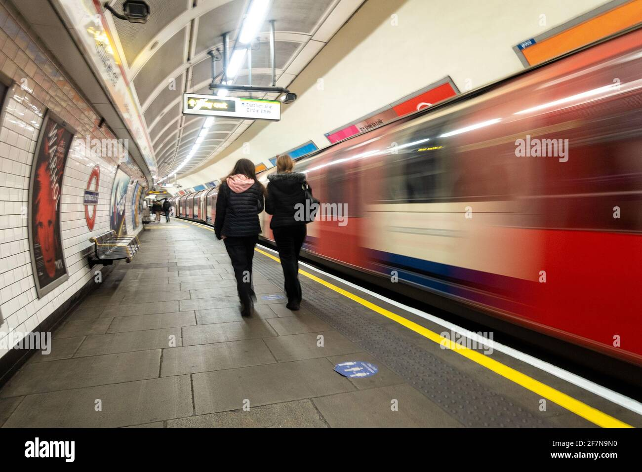 passengers-walk-along-the-platform-towards-the-exit-at-notting-hill-gate-london-underground-station-as-a-train-leaves-in-a-blur-2F7N9N0.jpg