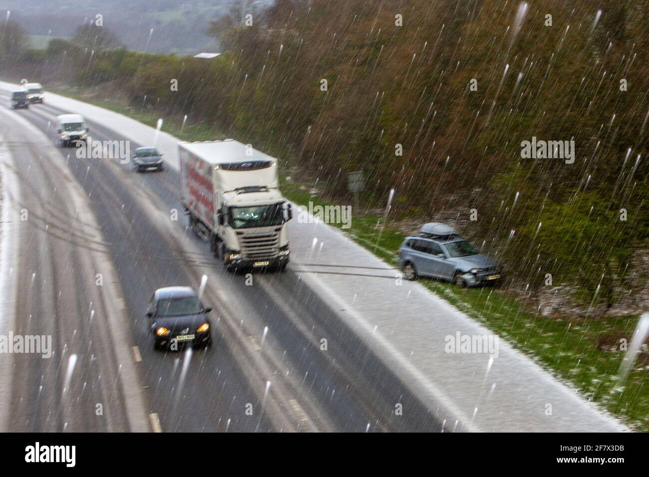 Chorley Lancashire. 10th April 2021 UK Weather;  Motorway mayhem as freak hail stone shower makes driving tricky with a series of collisions in Chorley. BMW 4 wheel drive vehicles in separate incidents collide with the armcor on the M61 central reservation. Credit MediaWorldImages/AlamyLivenews Stock Photo