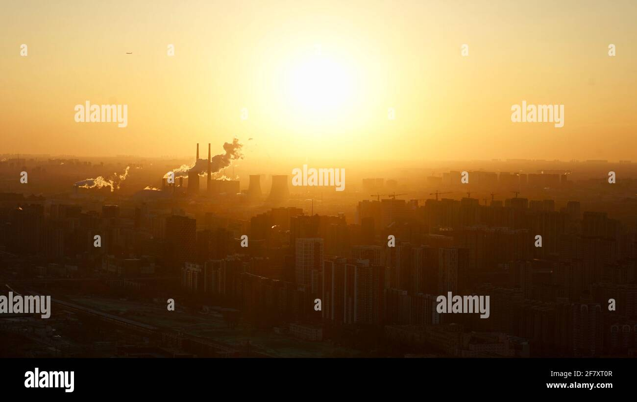 Sunrise in Beijing City with smoke coming out of tall chimneys. Stock Photo