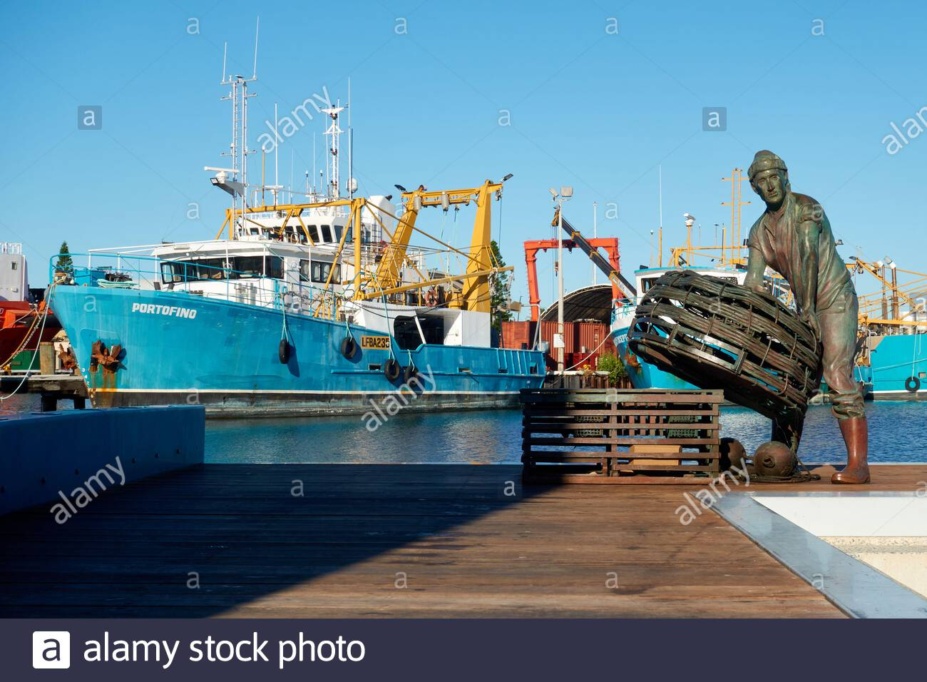 a-bronze-sculpture-by-greg-james-of-a-fisherman-with-craypots-for-lobster-fishing-and-the-portofino-fishing-boat-at-fremantle-fishing-boat-harbour-wa-2F8X55X.jpg