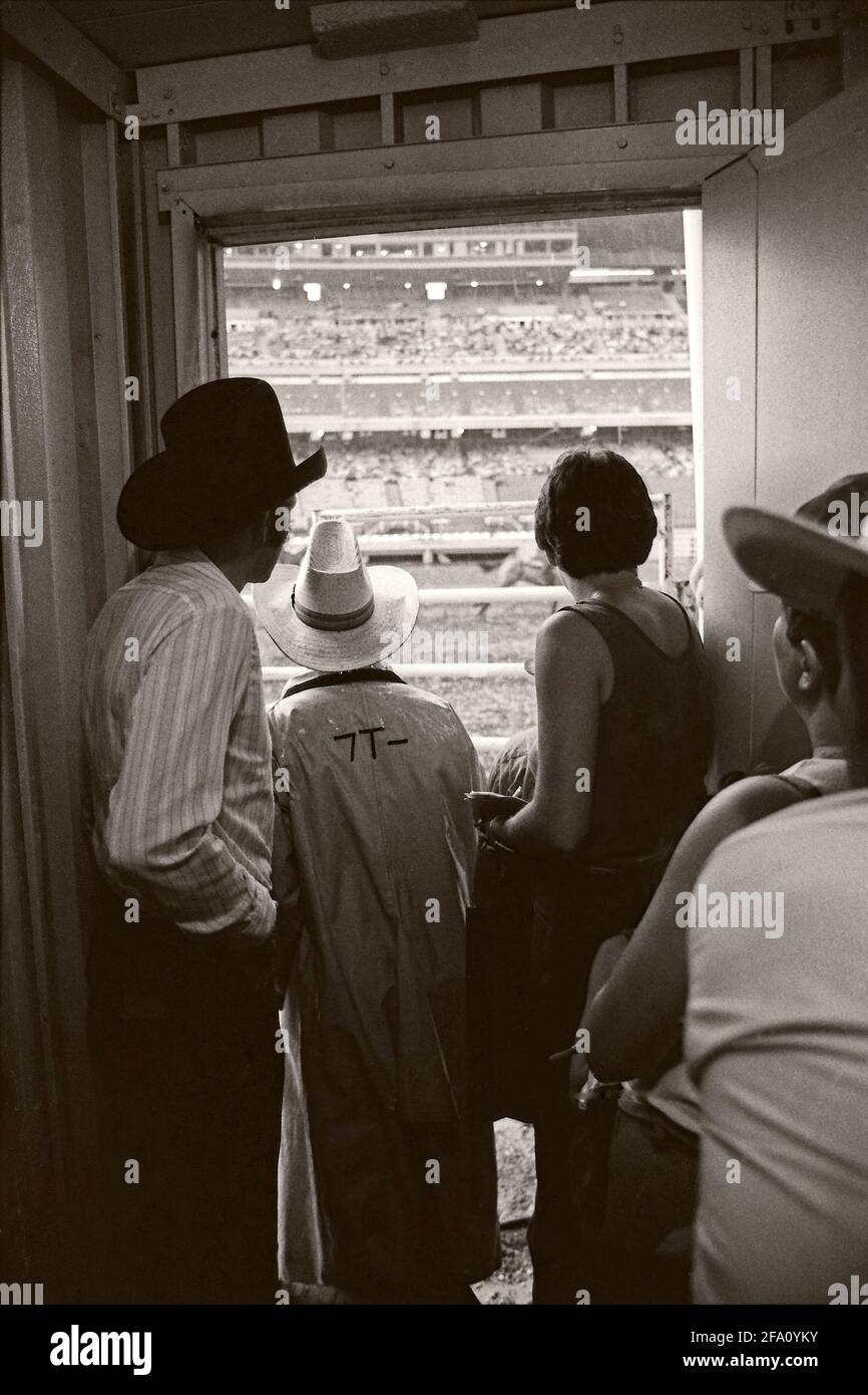 Rodeo spectators sheltering from the rain at the Calgary Stampede. Vintage monochrome circa 1980 Stock Photo