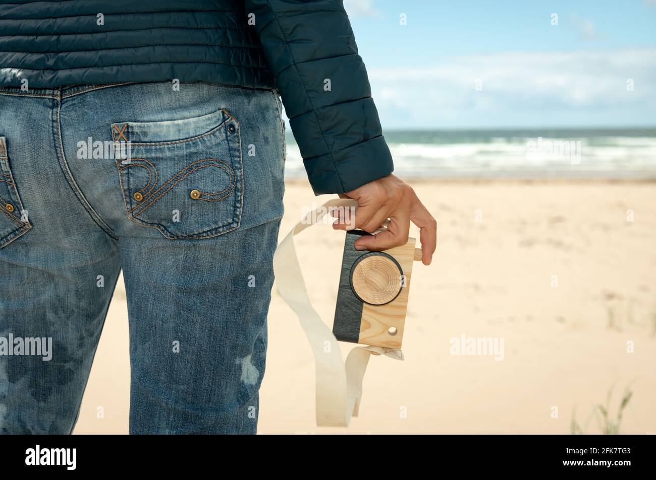 close-up-of-womans-hand-holding-an-wooden-toy-photo-camera-against-sandy-beach-background-fun-photography-concept-2FK7TG3.jpg