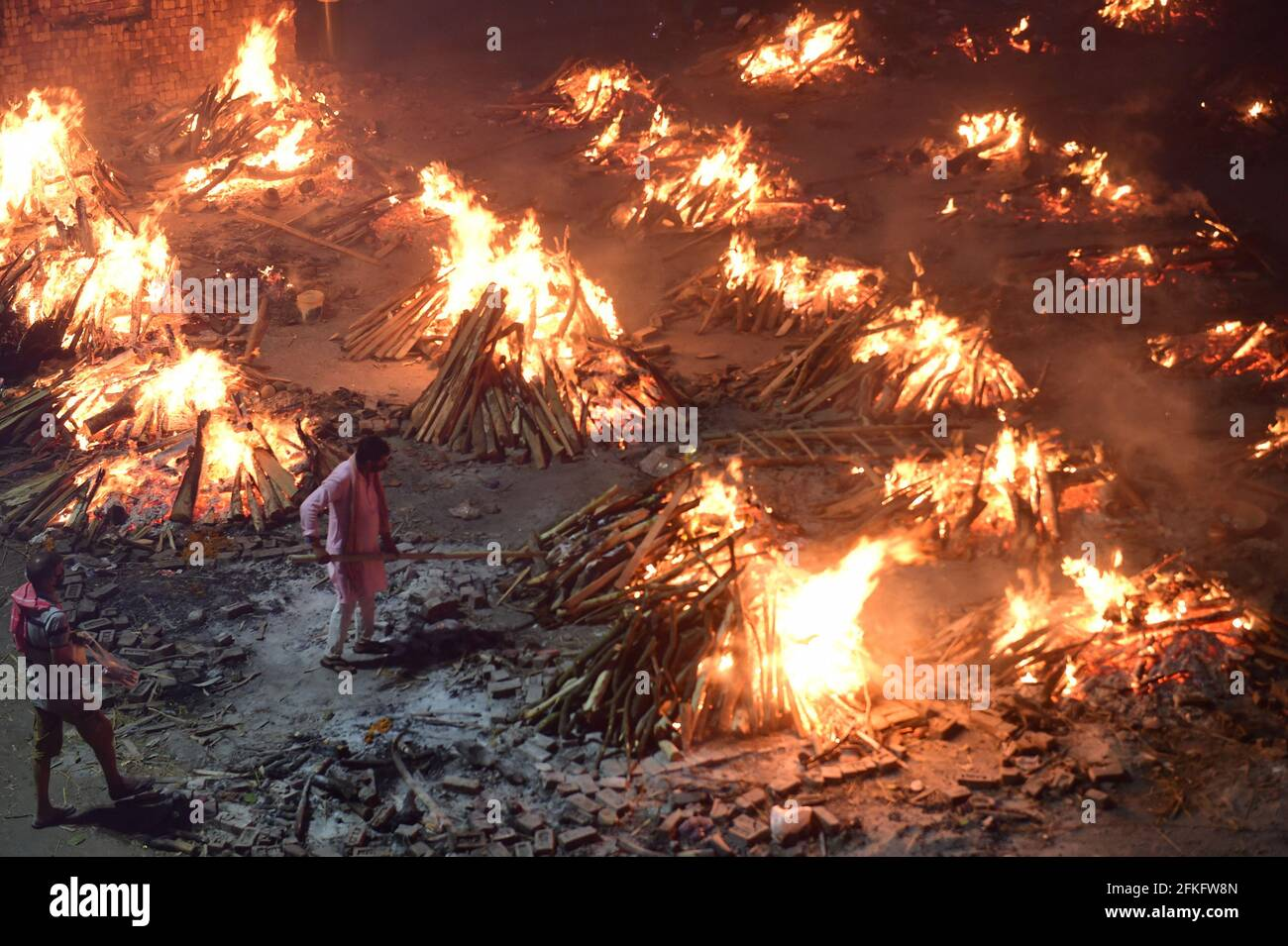 New Delhi, India. 01st May, 2021. Workers and family members bring bodies for cremation near multiple funeral pyres of victims of COVID-19 burn at a ground that has been converted into a crematorium for mass cremation in New Delhi, India on Saturday, May 1, 2021. Photo by Abhishek/UPI Credit: UPI/Alamy Live News Stock Photo