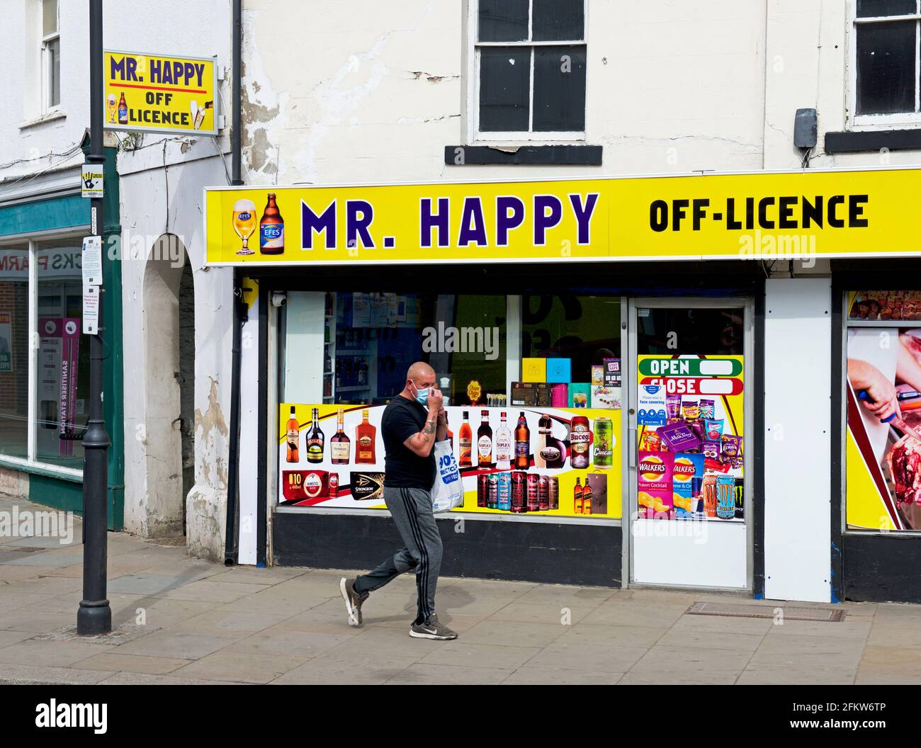 man-walking-past-shop-mr-happy-off-licence-in-thorne-south-yorkshire-england-uk-2FKW6TP.jpg