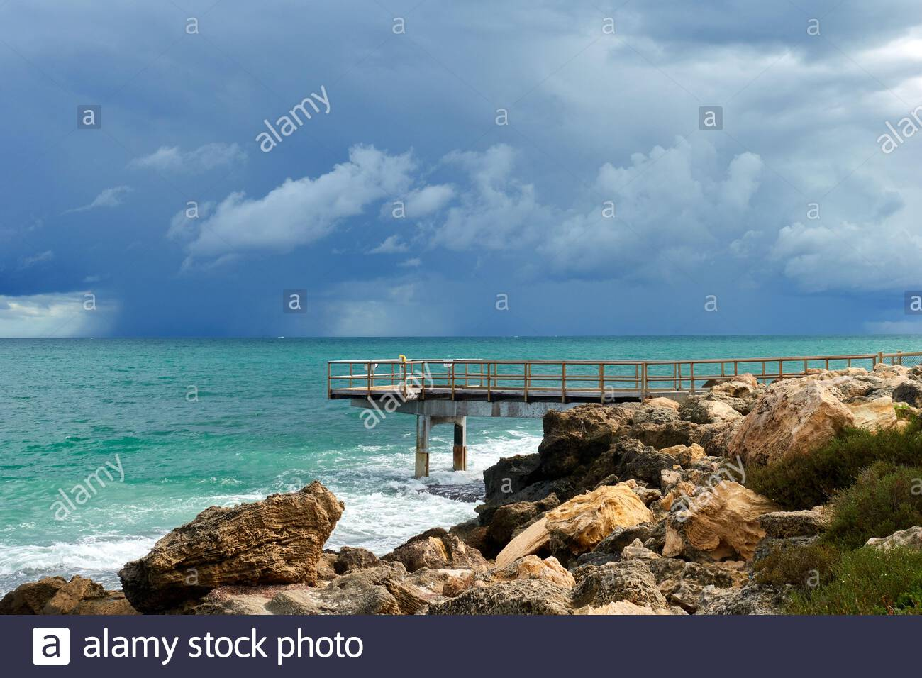 a-raincloud-out-to-sea-as-seen-from-north-beach-with-the-north-beach-jetty-in-the-foreground-perth-western-australia-2FMPK8C.jpg