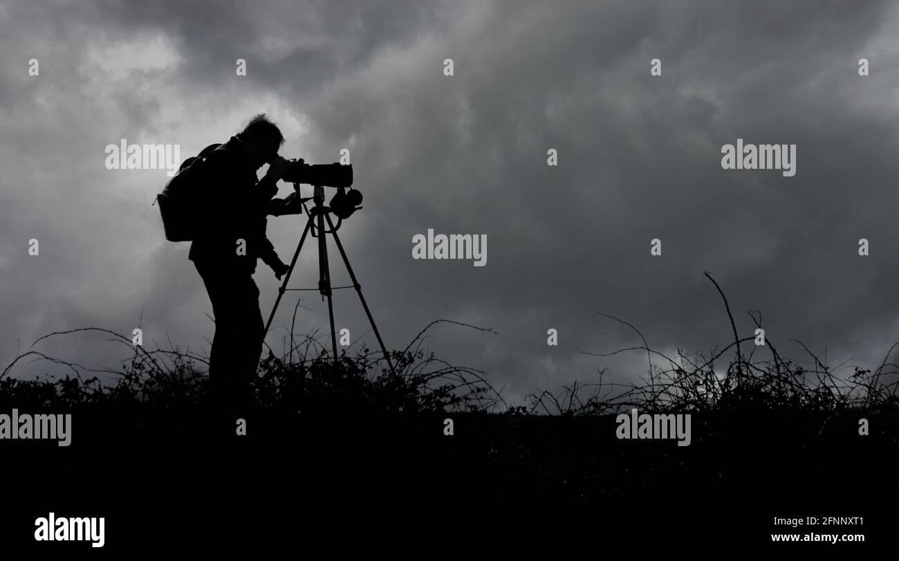 bird-watcher-twitcher-looking-through-a-telescope-on-a-tripod-on-the-horizon-against-a-dark-stormy-sky-uk-monochrome-black-and-white-2FNNXT1.jpg