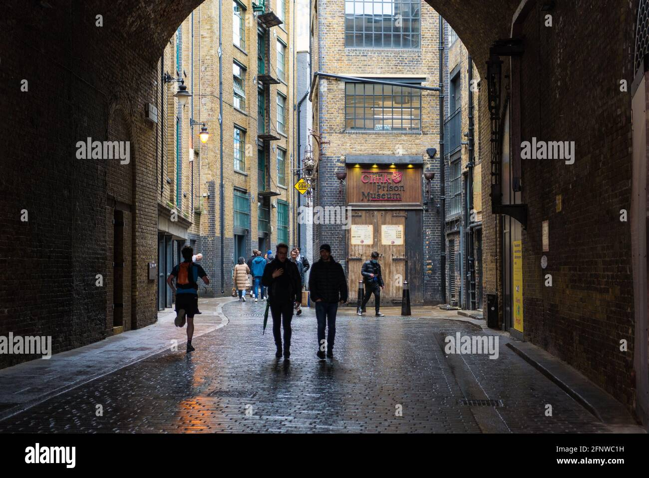 People walking in Clink Street, a narrow cobbled street in the Bankside district, London Borough of Southwark, England, UK Stock Photo