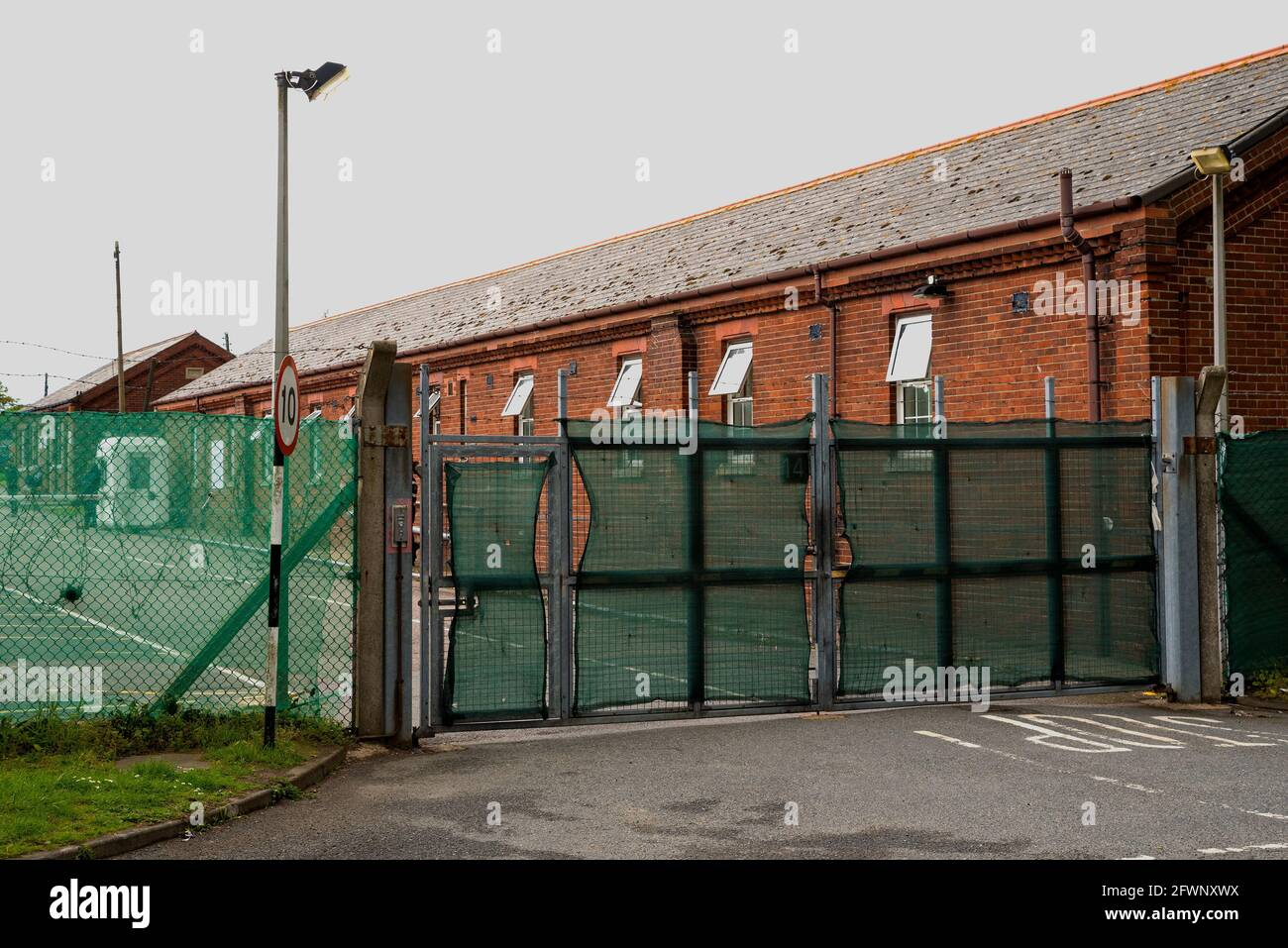since-september-2020-ex-mod-napier-barracks-folkestone-have-been-used-by-the-home-office-to-provide-temporary-accommodation-for-single-adult-male-refugees-who-are-seeking-uk-asylum-the-camp-is-operated-by-clearspring-ready-homes-previously-around-25-of-the-camps-refugees-have-tested-positive-for-covid-19-caused-by-a-serious-lack-of-facility-for-social-distancing-the-barracks-have-also-been-declared-unsuitable-for-human-accommodation-by-independent-inspectors-high-fencing-around-the-napier-barracks-is-topped-by-barbed-wire-pictured-gate-entrance-to-the-napier-barracks-2FWNXWX.jpg