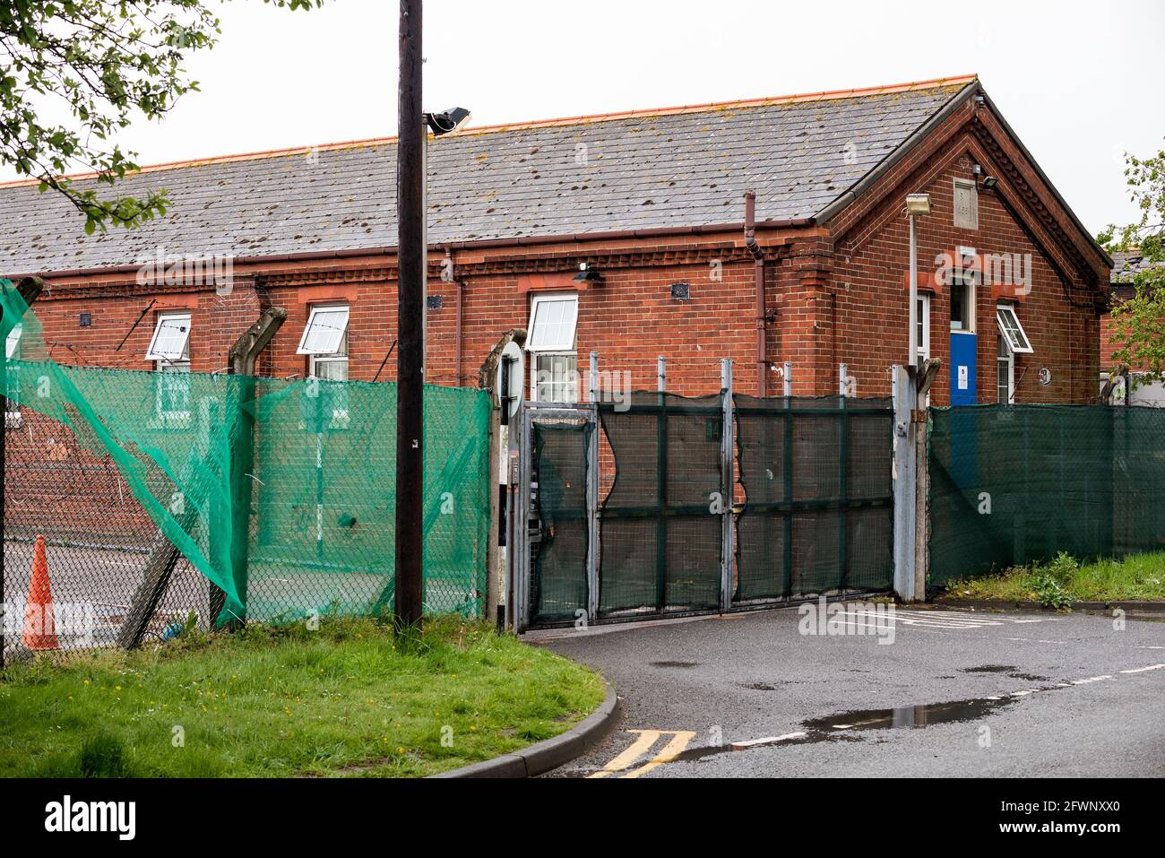 since-september-2020-ex-mod-napier-barracks-folkestone-have-been-used-by-the-home-office-to-provide-temporary-accommodation-for-single-adult-male-refugees-who-are-seeking-uk-asylum-the-camp-is-operated-by-clearspring-ready-homes-previously-around-25-of-the-camps-refugees-have-tested-positive-for-covid-19-caused-by-a-serious-lack-of-facility-for-social-distancing-the-barracks-have-also-been-declared-unsuitable-for-human-accommodation-by-independent-inspectors-high-fencing-around-the-napier-barracks-is-topped-by-barbed-wire-pictured-gate-entrance-to-the-napier-barracks-2FWNXX0.jpg