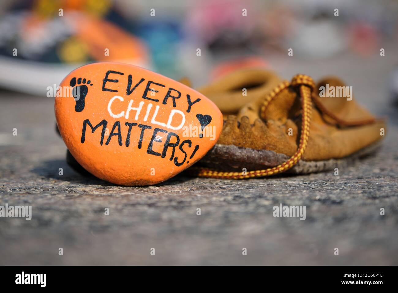 memorial-to-aboriginal-children-whose-remain-found-in-residential-schools-in-canada-child-moccasin-and-painted-orange-rock-left-in-memory-ottawa-2G66P1E.jpg
