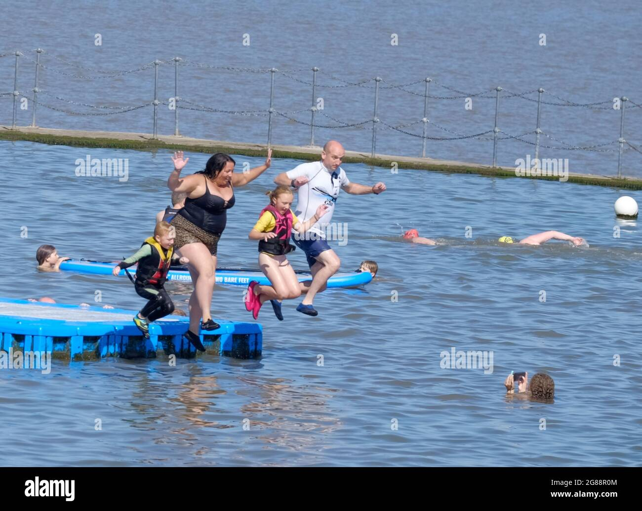 clevedon-somerset-uk-18th-july-2021-family-fun-clevedon-marine-lake-draws-in-people-looking-to-cool-down-on-a-very-hot-day-paddle-boarding-jumping-in-and-swimming-are-on-the-family-fun-agenda-before-freedom-day-tomorrow-credit-jmf-newsalamy-live-news-2G88R0M.jpg