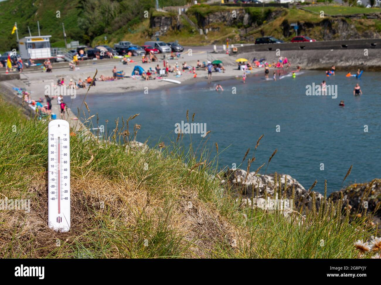 crowded-beach-with-thermometer-in-foreground-showing-very-hot-day-2G8PYJY.jpg