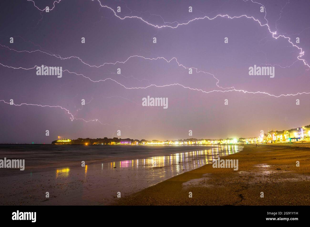 Weymouth, Dorset, UK.  24th July 2021.  UK Weather.  Streaks of lightning fills the sky above the seaside resort of Weymouth in Dorset as heavy rain and thunderstorms pass through overnight as the weeklong heatwave ends with a bang.  Picture Credit: Graham Hunt/Alamy Live News Stock Photo