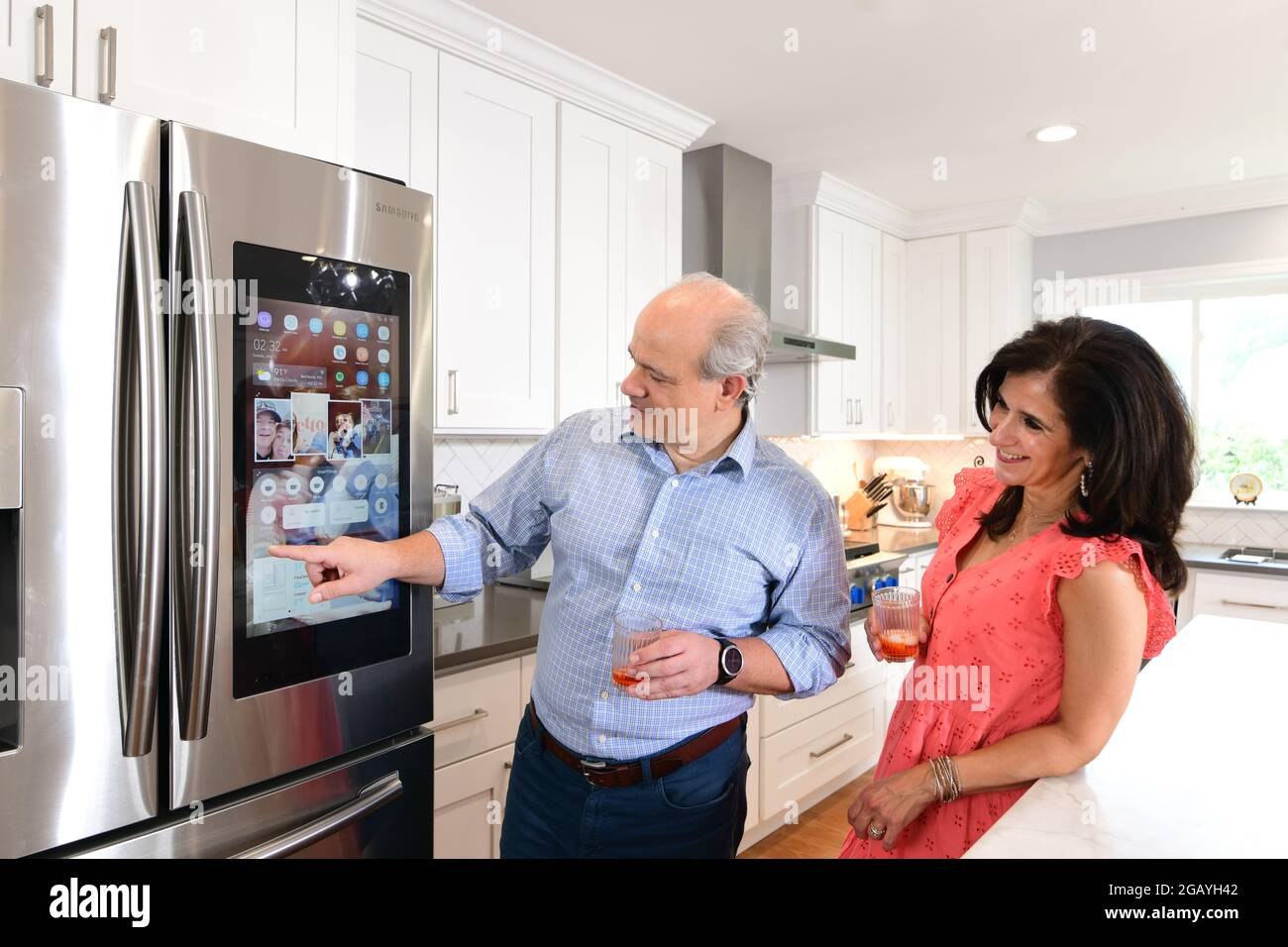 a-couple-uses-a-samsung-smart-refrigerator-in-their-home-kitchen-with-a-touch-screen-and-wifi-2GAYH42.jpg