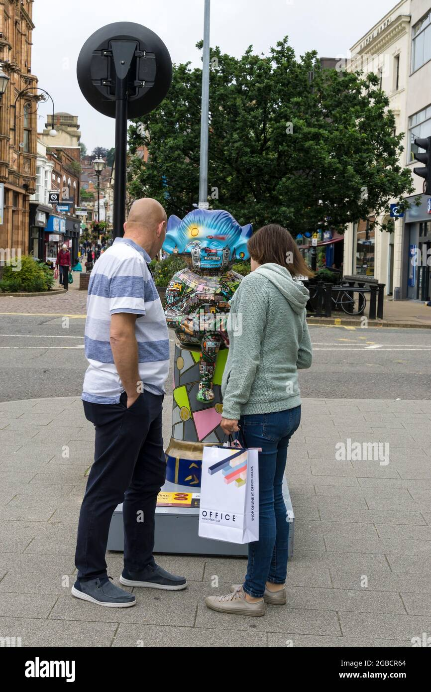 couple-looking-at-the-running-imp-one-of-the-lincoln-imp-trail-decorated-statues-2021-2GBCR64.jpg