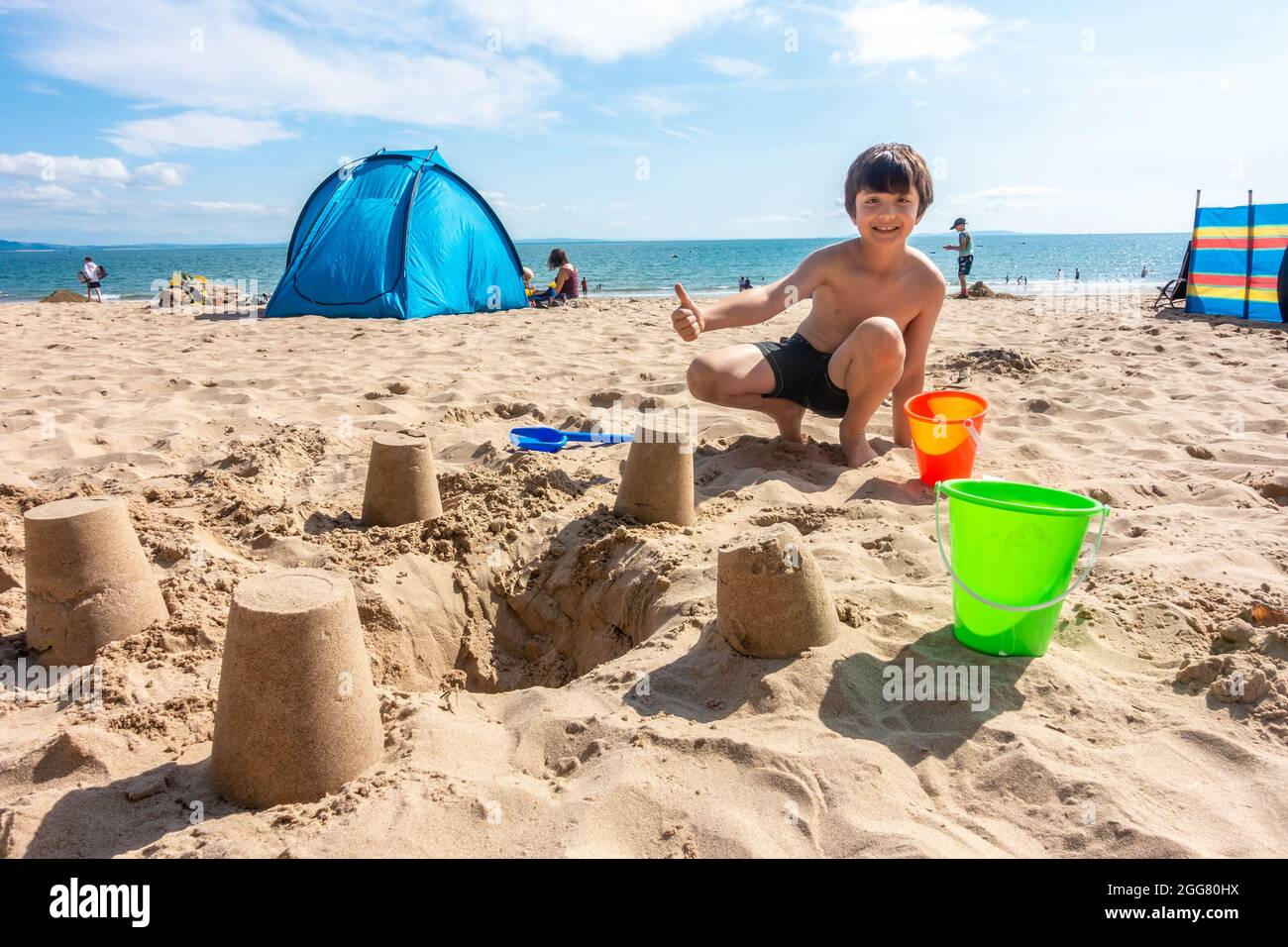 a-young-boy-poses-proudly-with-the-sand-castles-that-he-has-made-on-the-north-beach-at-tenby-in-pembrokeshire-wales-uk-2GG80HX.jpg