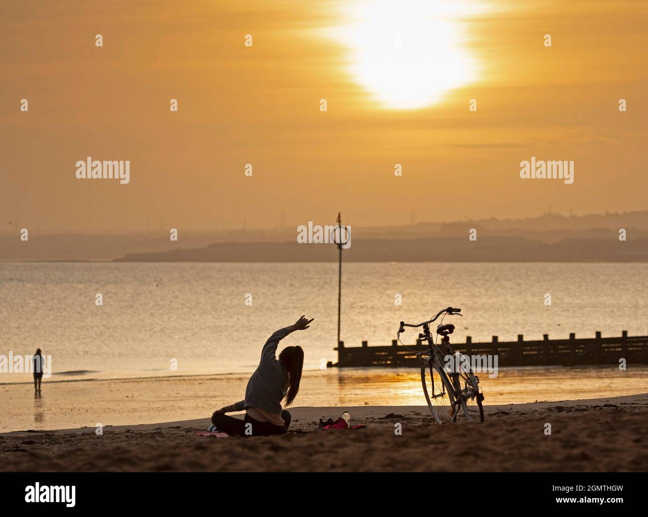 Portobello, Edinburgh, Scotland, UK weather. 21st September 2021.Temperature of 10 degrees centigrade, a young female cyclist takes yoga exercise on the sandy beach just after sunrise by the Firth of Forth. Credit: Arch White/Alamy Live News. Stock Photo