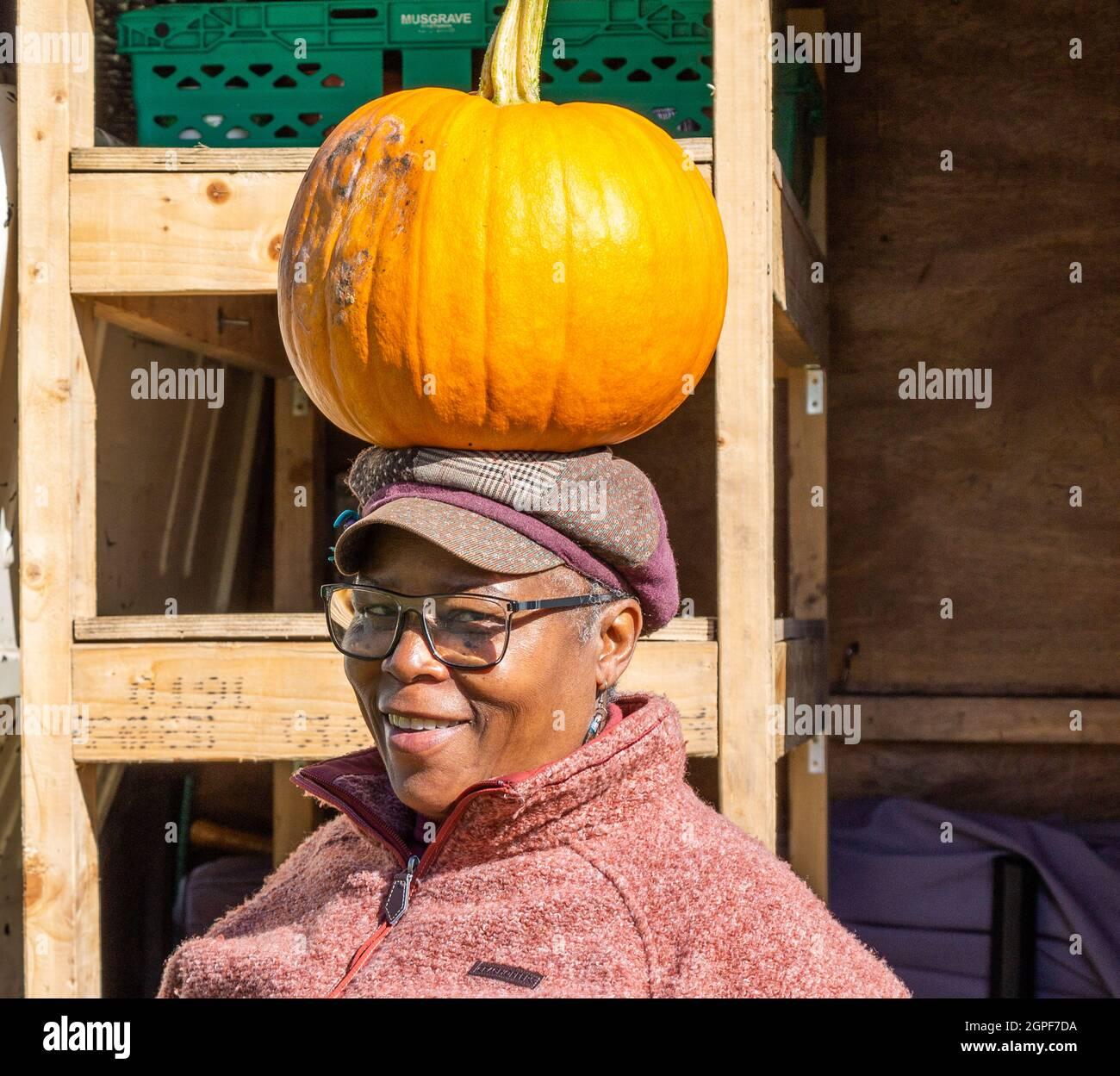 senior-woman-selling-pumpkins-balancing-a-pumpkin-on-her-head-2GPF7DA.jpg