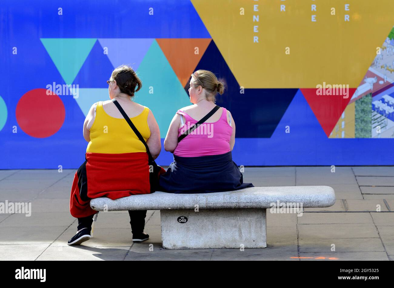 London, England, UK. Two colourful women sitting in front of a colourful wall in Oxford Street on a sunny day in October [no model release] Stock Photo