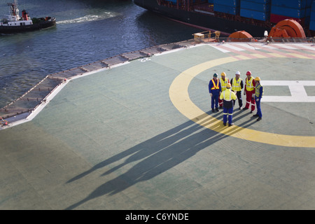 Workers talking on helipad of oil rig - Stock Image