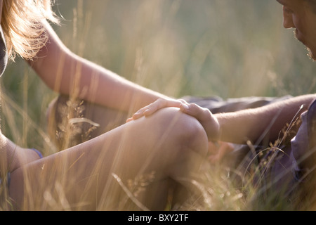 Detail of a young couple outdoors, mans hand on the womans knee - Stock Image