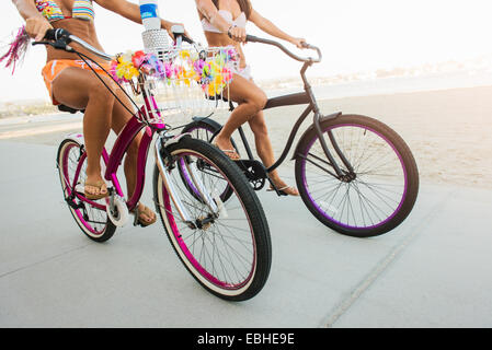 Neck down view of two women cyclists on beach, Mission Bay, San Diego, California, USA - Stock Image
