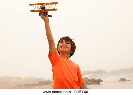 Boy wearing orange t shirt playing with toy plane - Stock Image
