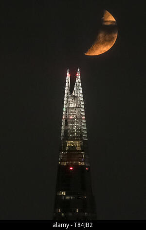 London, UK. 11th May, 2019. UK Weather: A Waxing Crescent moon appears briefly through heavy cloud over The Shard skyscraper building as it continues to set in the early hours of Saturday following a north westerly direction. Credit: Guy Corbishley/Alamy Live News - Stock Image